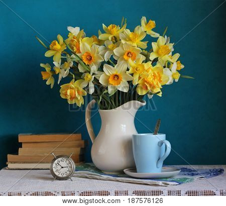 The varietal bouquet of yellow daffodils in a white jug alarm clock and books on the table. Still life.