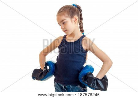 little girl with pigtail stands sideways looks down and keeps her hands on the sides of the boxing gloves on white isolated isolated on white background.