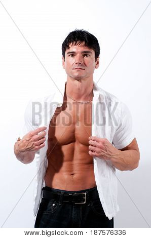 The contemporary man is taking off his shirt.