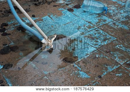 Swimming pool sludge removal with a vacuum cleaning brush and hose