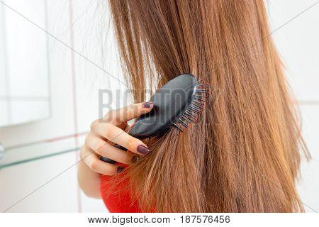 young girl combing her long hair closeup
