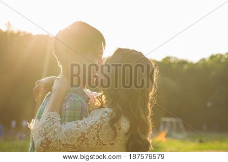 Young attractive couple in love kissing in summer in field.