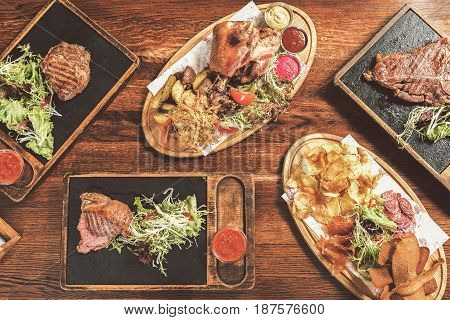 Abundance. Top view of mix of delicious grilled meat meals. Snacks for beer served on cutting board. Pork knuckle with fried potato wedges and mix salad and boiled cabbage are on wooden plate
