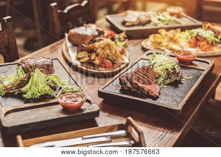Tasty mix. Close up of grilled meat meals are on wooden table. Focus on juicy medallion and appetizing steak