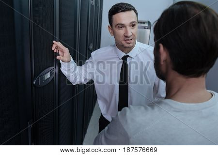 Pleasant interaction. Joyful nice friendly man smiling and speaking with colleague while discussing their job in the data center