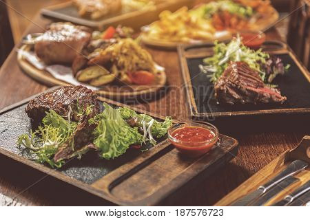 Great meat feast. Close up of succulent fragrant medallion with lettuce and red sauce. Appetizing grilled dishes with fresh salad served on desk