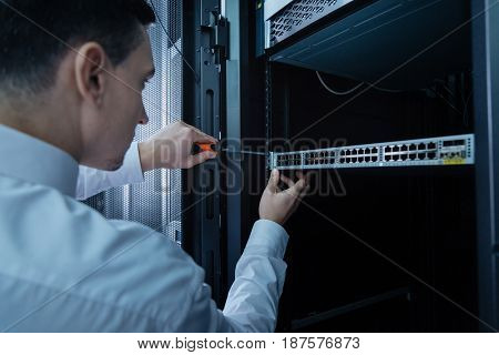 Server repair. Handsome professional male engineer holding a screwdriver and using it while repairing a rack server
