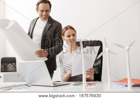 Work in cooperation. Positive woman sitting at the table while working together with her collegue on the project of wind turbines