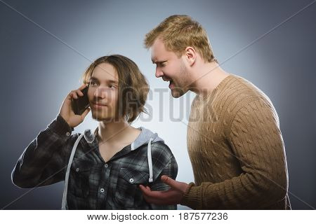 Angry man yells at a teen with a mobile phone. isolated on gray background
