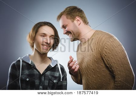 Kind man talking to a happy teenager on gray background. Communication concept. Positive human emotion, facial expression. Closeup. Communication concept.