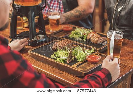 Succulent meat dish. Close up of appetizing grilled medallion, fresh salad and tomato sauce on wooden board. Adult man sitting with friends in pub and holding knife and fork
