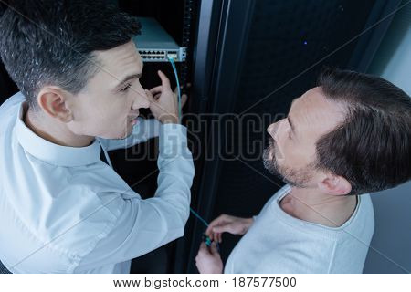 Asking for advice. Handsome positive young man looking at his colleague and pointing at the rack server while asking for advice