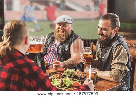 Fun together. Cheerful bearded guys laughing while drinking beer in pub. They watching football while enjoying food