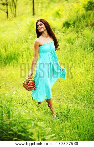 Beautiful young woman walking on summer grass field with basket of paprica