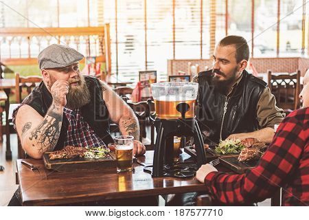 Meeting of best friends. Three stylish bearded men in casual wear talking and drinking beer while sitting in bar together. They relaxing after work