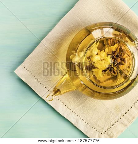 A square overhead photo of a teapot with a tea flower in it, with a place for text
