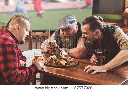 Animal instinct. Three mature bearded guys sitting around table and looking at roasted knuckle of pork. They expressing aggression and trying to gnaw the meat off the bone