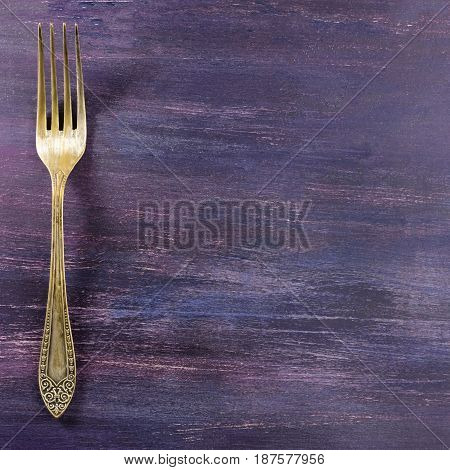 A square overhead photo of a vintage fork on a purple wooden background texture. A restaurant menu or special offer banner design template