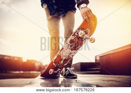 Moscow, Russia - May 20, 2017: male skateboarder guy is holding a skateboard at sunset or sunrise. Concept active rest. Wipes and holes on the shoe.