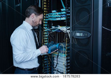 Everything must be in order. Professional handsome male engineer holding a special device and doing a system check while standing near the server rack
