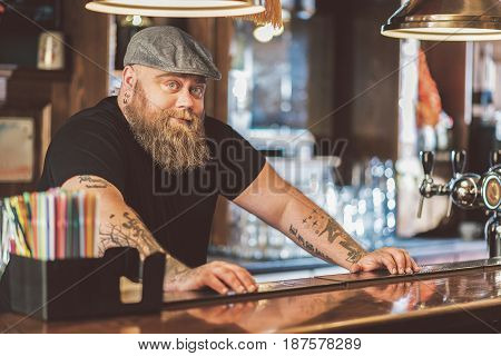 Boring at work. Portrait of tattooed fat bartender expressing anticipation while leaning on bar counter. He looking at camera confidently