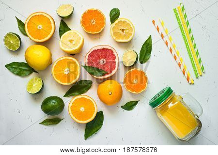 Citrus juice smoothie and ingredients on white. Fruit food background. Healthy eating. Top view