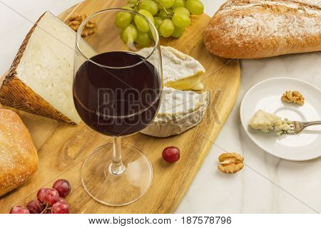 A photo of a wine and cheese tasting, with bread, grapes, a glass of red wine, and a place for text