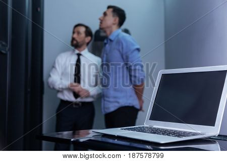 Electronic device. Modern innovative laptop lying on the table with two professional male technicians standing in the background