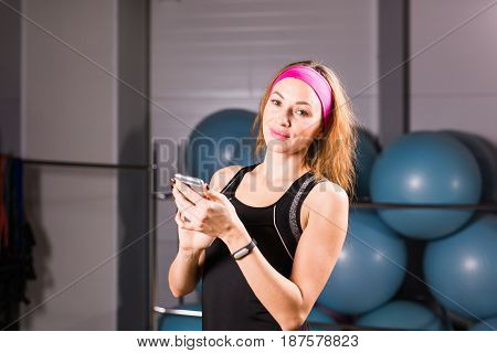 sport, fitness, technology and people concept - young woman with activity tracker and smartphone in gym.