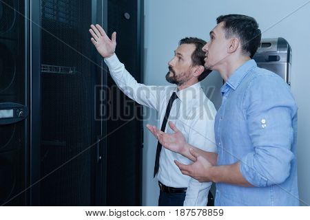 Here is it. Handsome nice bearded man standing with his colleague and speaking to him while pointing at the data server