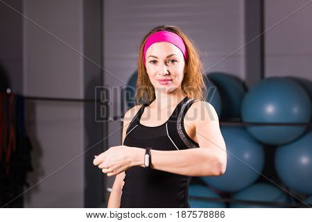 Woman using activity tracker or heart rate monitor. Indoors fitness concept.