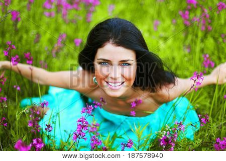 woman sitting on summer flower field