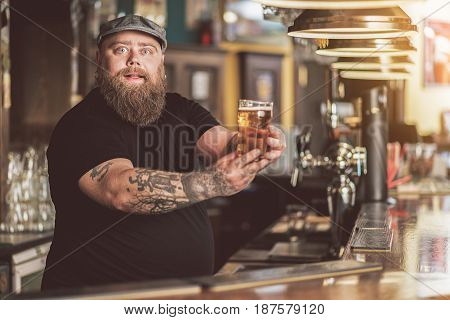 Wonderful lager. Portrait of bearded tapster holding cold glass of beer. He looking at camera admiringly