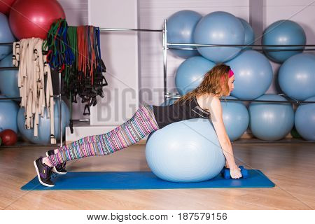 Young sporty woman in gym doing fitness exercice with blue ball.