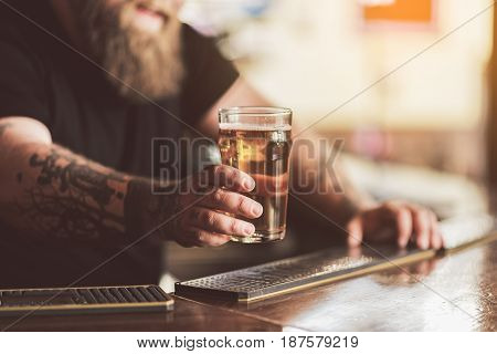 Beverage for you. Close up of hand of man holding glass of cold beer. He standing at counter in beerhouse