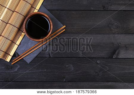 Background for sushi. Bamboo mat, soy sauce, chopsticks on dark table. Top view with copy space