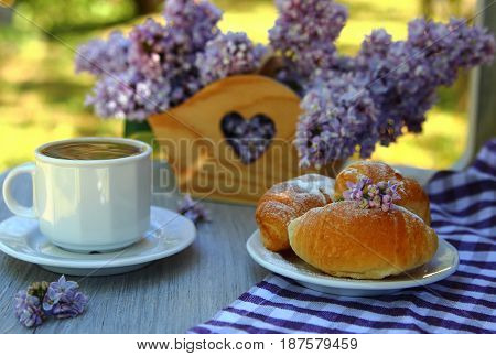 a croissant with a bouquet of lilacs and Cup of coffee on the table in the garden