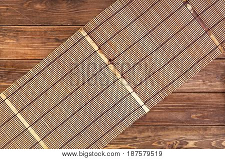 Bamboo mat for sushi on wooden background. Top view with copy space