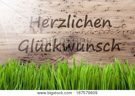 German Text Herzlichen Glueckwunsch Means Congratulations. Spring Season Greeting Card. Bright, Sunny And Aged Wooden Background With Gras.