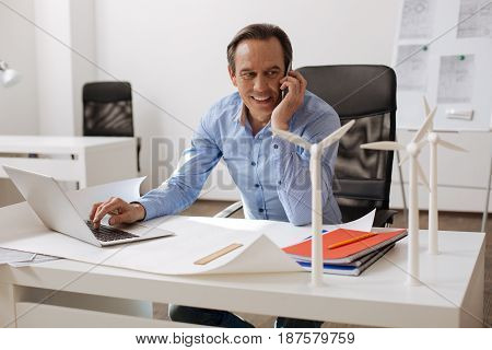 Positive workign days. Cheerful delighted engineer sitting at the table and talking on cell phone while working on the laptop