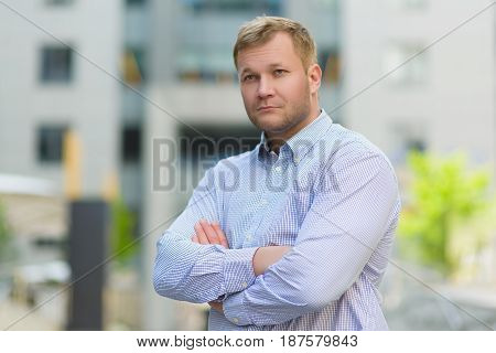 Portrait of serious Handsome businessman in blue shirt standing in front of office building.