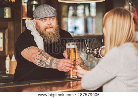 Mysterious client. Fat adult bartender and blonde woman from the back. Pleasant fat man stretching out mug of tasty ale for lady while looking at her with slight smile