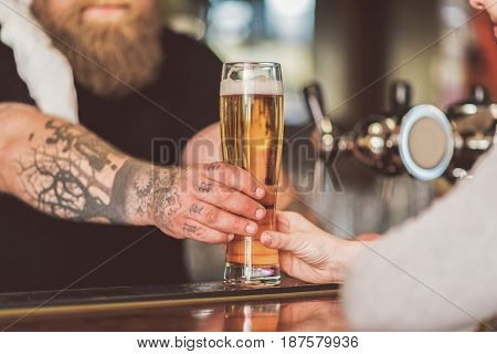 Freshly tapped beer. Close up of glass with cold lager. Fat bearded man working as bartender stretching out mug of tasty ale for woman