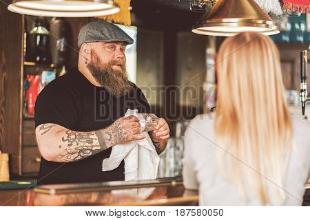 Exciting talking. Selective focus on joyful bartender wiping glass while communicating with blonde lady. He looking at woman playfully