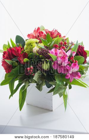 A beautiful bouquet of red roses and astermers in a flowerpot on a white background.