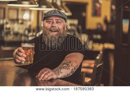 Cheers. Portrait of cheerful bearded man holding glass of beer and smiling. He sitting at bar counter and looking at camera with joy
