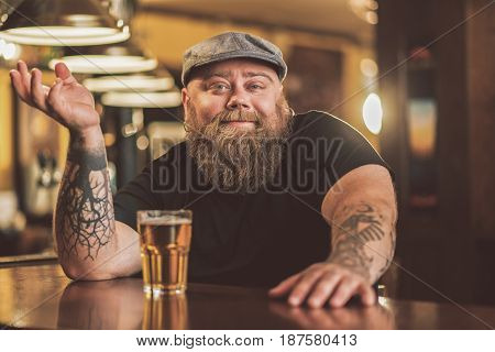 Be yourself. Portrait of joyful obese man gesturing positively while sitting at bar counter. He looking at camera cheerfully