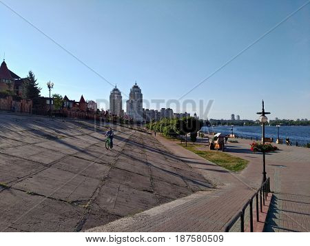Obolonskaya embankment in Kiev, Ukraine. The boy rides a bicycle along the concrete embankment near the Dnieper River