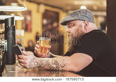 Bad news. Depressed bearded man expressing disappointment while looking at screen of mobile phone. He sitting at bar counter while drinking lonely