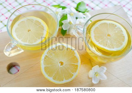 Two mugs of tea with lemon early in the morning on the table